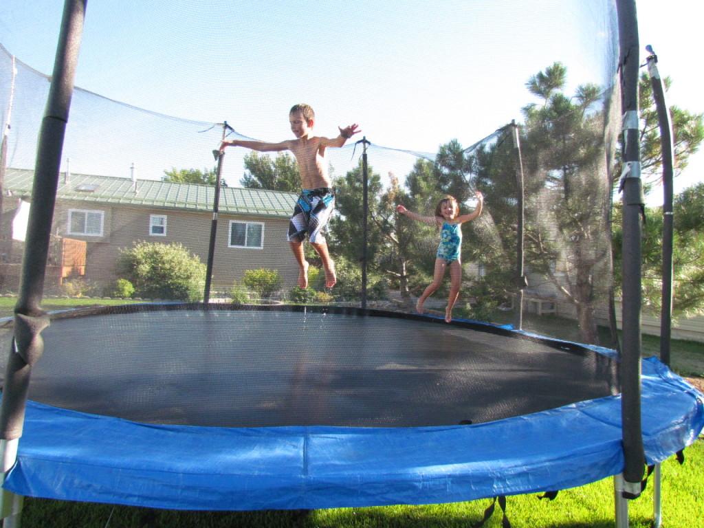 Image of kids on a trampoline and sprinkler