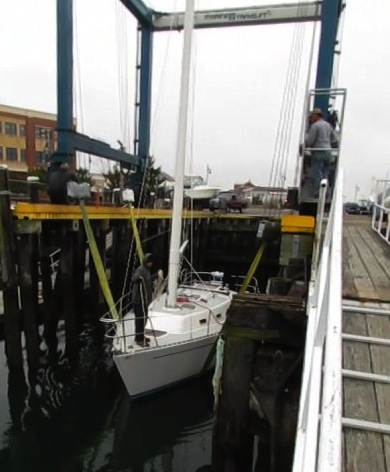 Image of sailboat being lowered into the the water via travel lift. AKA splash