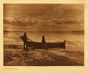 Pulling a rowboat onto the beach, Edward S. Curtis Puget Sound