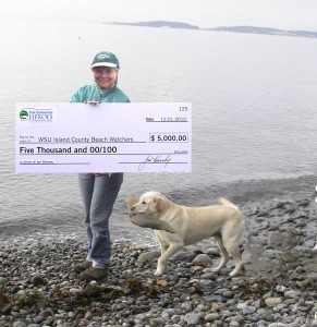 Image of Jan Holmes on beach with huge check from Cox Conserves