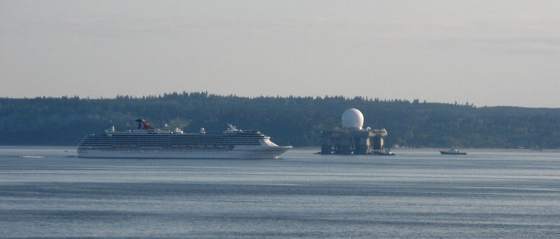 a huge radar dome passes a cruise ship