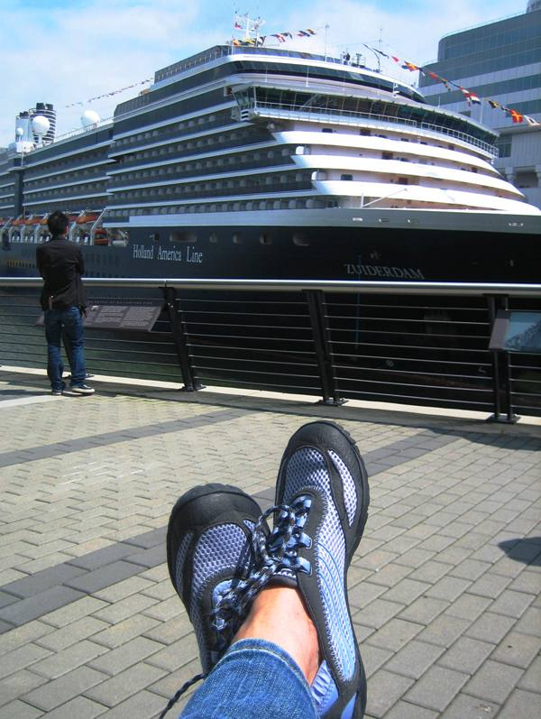 a Holland America cruise ship is background to a pair of Merrell barefoot running shoes in Vancouver BC