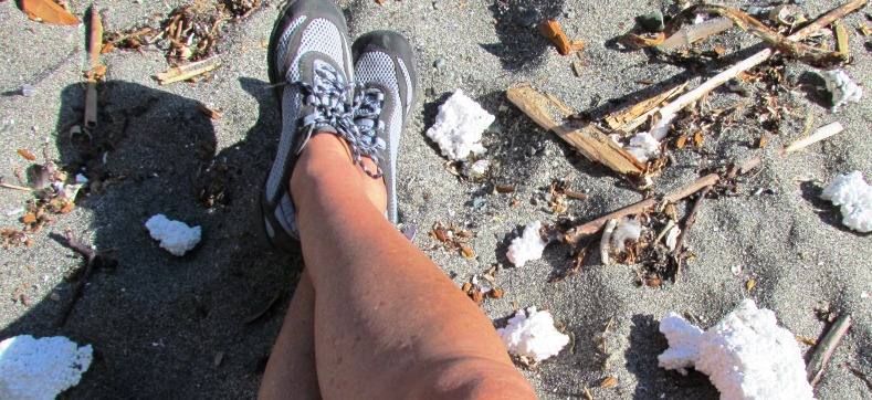 Image of chunks of Styrofoam breaking up on a sandy beach.