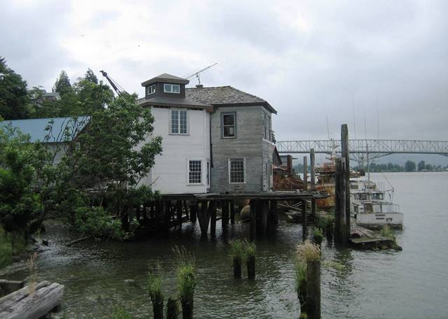 A handmade house stands on pilings in the Columbia River