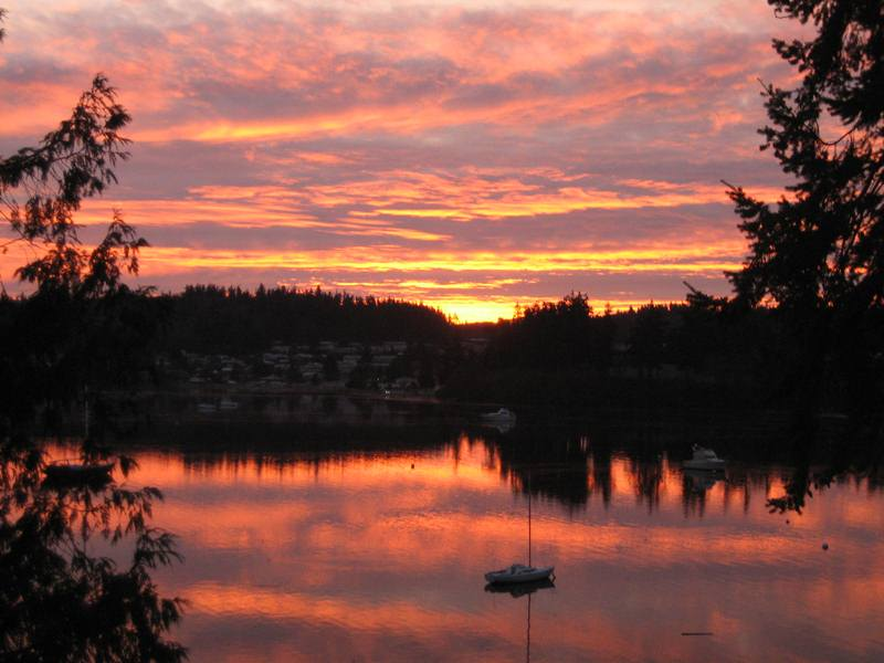 Image of firey December sunrise over harbor and sailboat at anchor