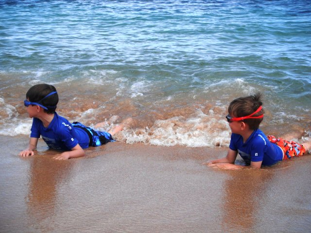 Image of children playing in Hawaii surf an antidote to Northwest Winter