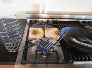 When no toaster is available ingenuity must take over. Cake rack supported over flame works fine.