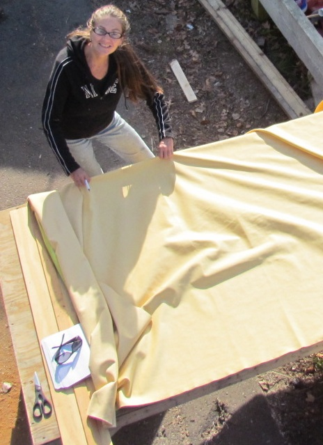 Image of woman laying out fabric for sewing boat cushions on Thanksgiving