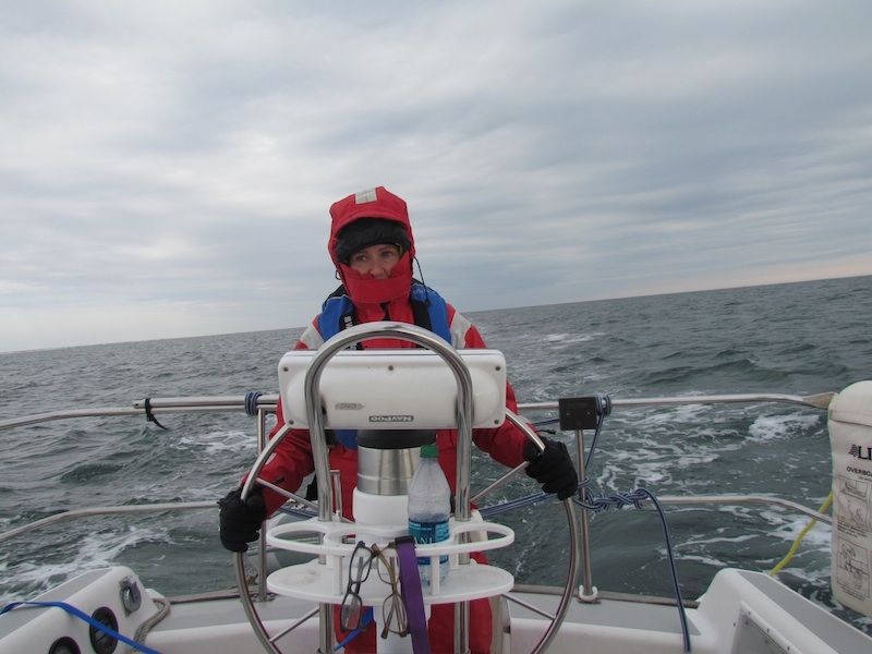steering a sailboat wearing red foul weather gear