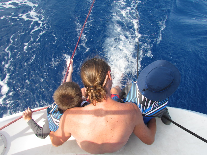 kids riding on stern of sailboat
