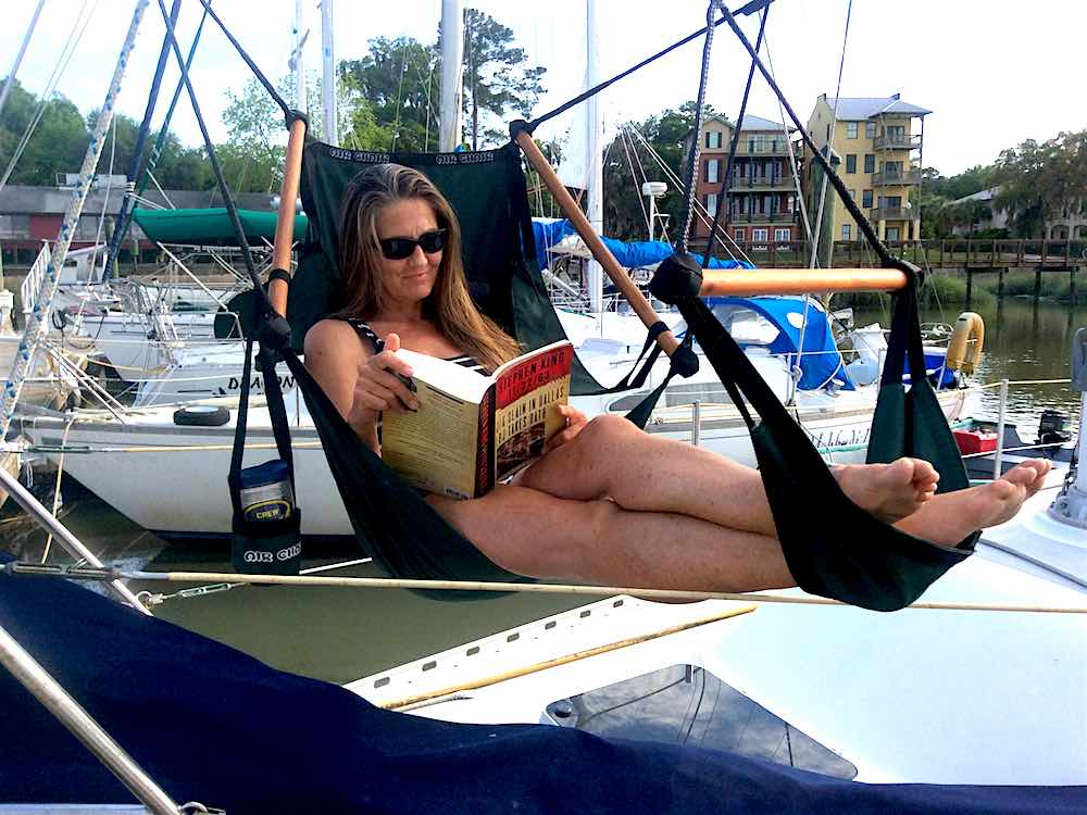 reading in the air chair on bow of sailboat