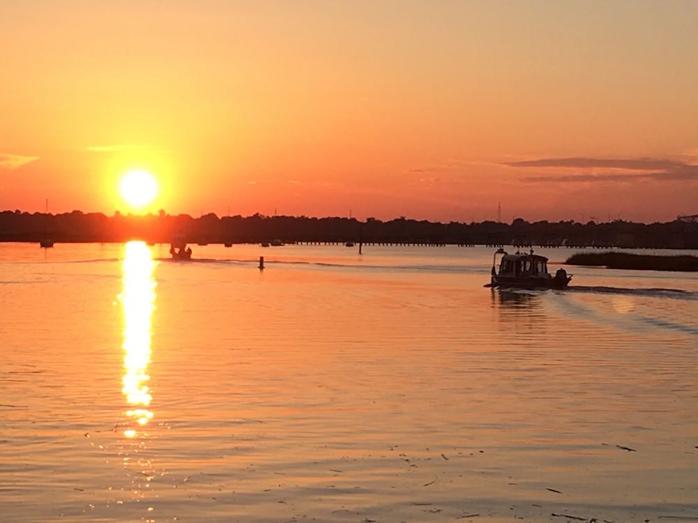 oil spill cleanup crew boats at sunset